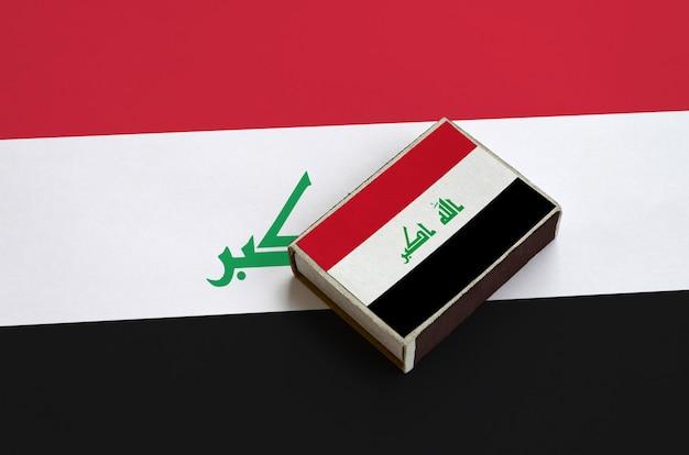 La bandiera dell'iraq è raffigurata su una scatola di fiammiferi che si trova su una grande bandiera