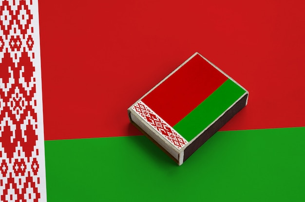 La bandiera della bielorussia è raffigurata su una scatola di fiammiferi che si trova su una grande bandiera