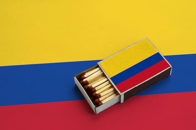 La bandiera della colombia è mostrata in una scatola di fiammiferi aperta, che è piena di fiammiferi e si trova su una grande bandiera