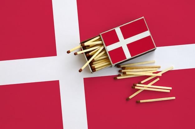 La bandiera della danimarca viene mostrata su una scatola di fiammiferi aperta, dalla quale cadono diverse partite e si trova su una grande bandiera