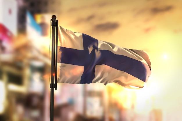 La bandiera della finlandia contro la città sfocata alla luce all'illuminazione di sunrise