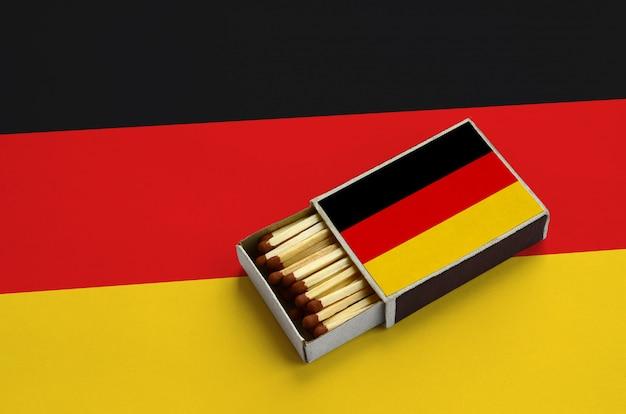 La bandiera della germania è mostrata in una scatola di fiammiferi aperta, che è piena di fiammiferi e si trova su una grande bandiera