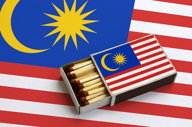 La bandiera della malesia è mostrata in una scatola di fiammiferi aperta, che è piena di fiammiferi e si trova su una grande bandiera