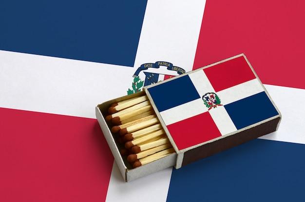 La bandiera della repubblica dominicana è mostrata in una scatola di fiammiferi aperta, che è piena di fiammiferi e si trova su una grande bandiera