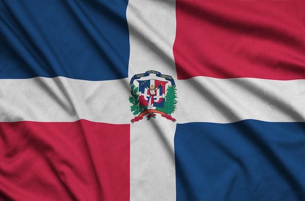 La bandiera della repubblica dominicana è raffigurata su un tessuto sportivo con molte pieghe.