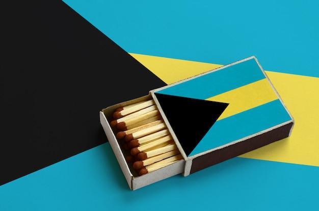 La bandiera delle bahamas è mostrata in una scatola di fiammiferi aperta, che è piena di fiammiferi e si trova su una grande bandiera