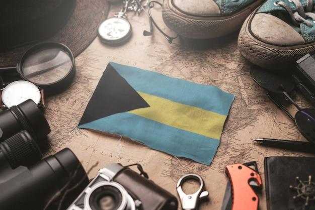La bandiera delle bahamas tra gli accessori del viaggiatore sulla vecchia mappa vintage. concetto di destinazione turistica.