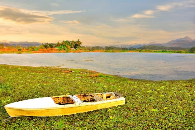 La barca a remi bianca sul lago ha uno sfondo montuoso.
