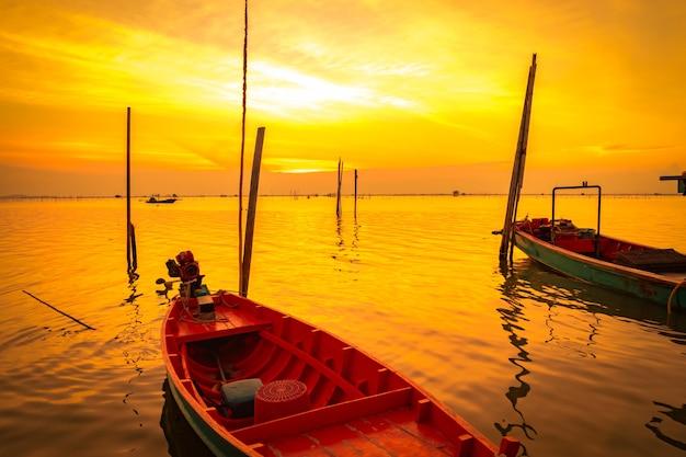La barca del pescatore che galleggia nel mare vicino al palo di bambù al tramonto
