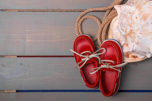 La barca rossa calza vicino alle grandi coperture e corda su fondo di legno. vista dall'alto/. copia spazio. telaio.