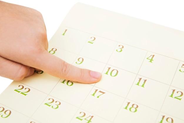 La barretta della femmina che mostra data in un calendario su fondo bianco. numero nel calendario