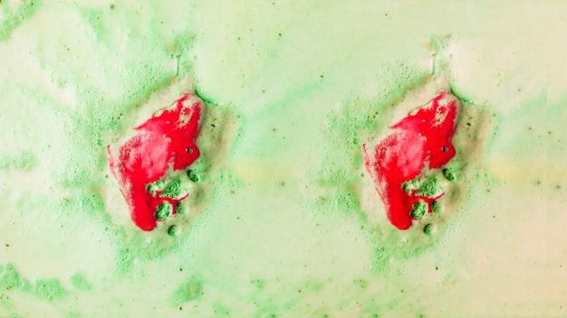 La bathbomb rossa si dissolve in acqua di bagno verde della bolla