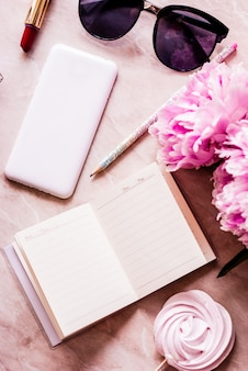 La beauty flat era con un diario, uno smartphone, accessori e peonie su uno sfondo di marmo