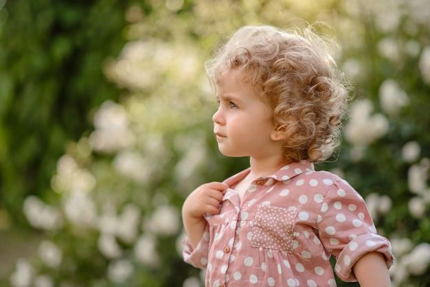 La bella bambina con i capelli biondi e ricci in passeggiata nel parco in una calda giornata estiva
