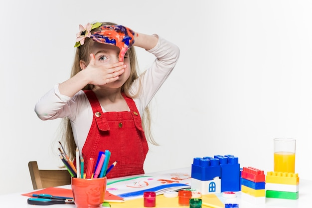 La bella bambina con le mani nella vernice