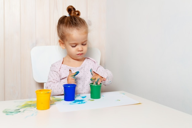 La bella bambina disegna con le pitture della barretta su un foglio di carta bianco