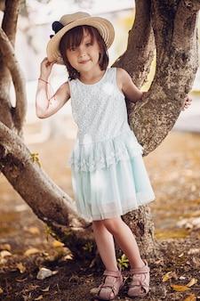 La bella bambina in un cappello e un vestito bianco sta vicino ad un albero un bello giorno caldo di autunno