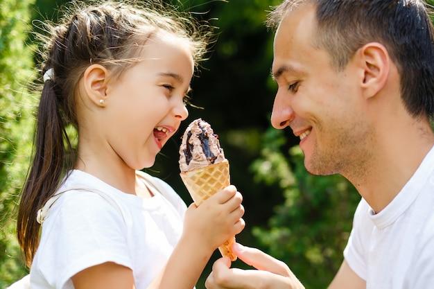 La bella bambina mangia il gelato in estate