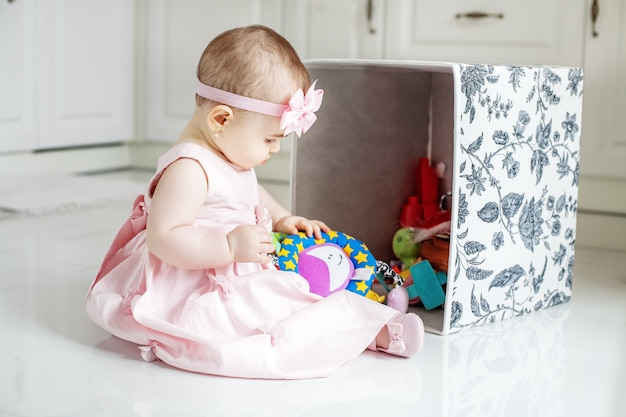 La bella bambina prende i giocattoli dalla scatola. vestito rosa.