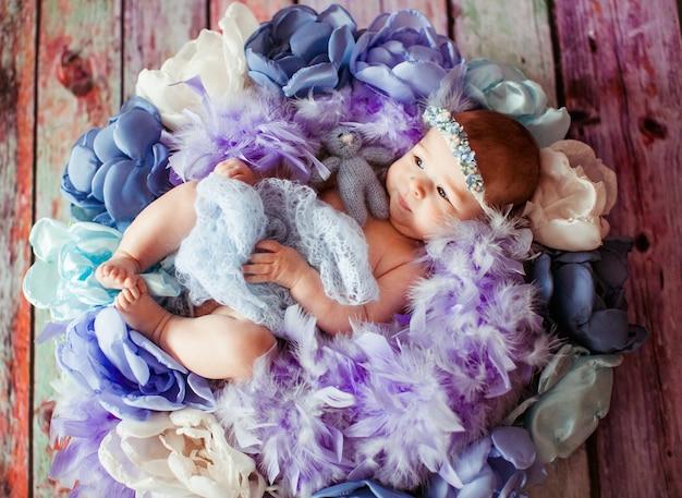 La bella bambina si trova tra vestiti viola, blu e rosa