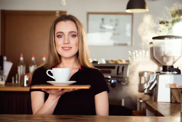 La bella barista femminile sta lavorando nella caffetteria. la donna attraente è in piedi dietro il bancone del bar, fa il caffè e accoglie i clienti.