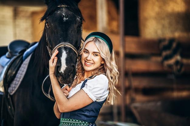 La bella bionda in abito tradizionale si prende cura del grande cavallo nero della fattoria