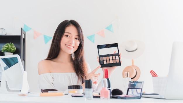 La bella blogger asiatica della donna sta mostrando come compensare e utilizzare i cosmetici.
