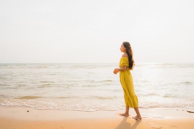 La bella camminata asiatica della giovane donna del ritratto sull'oceano del mare e della spiaggia con il sorriso felice si distende