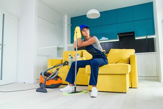 La bella casalinga stanca della pulizia si siede sul divano e si appoggia alla scopa dopo aver finito di lavare il pavimento.