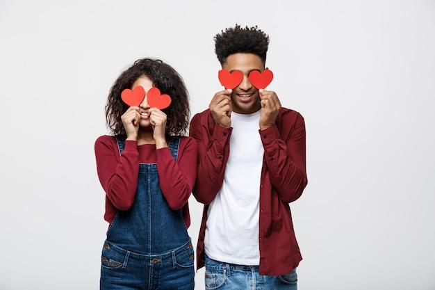 La bella coppia afroamericana afro sta tenendo i cuori di carta rossi e sorridere