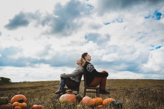 La bella coppia amata seduta sulle sedie vicino ai meloni
