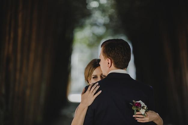 La bella coppia innamorata che abbraccia nella foresta