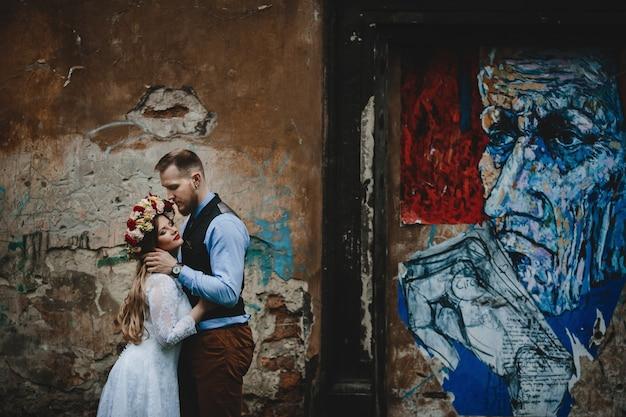 La bella coppia innamorata che abbraccia vicino al muro