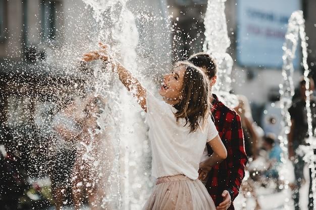 La bella coppia innamorata che gioca con la fontana