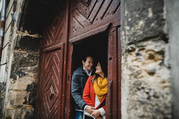 La bella coppia innamorata che si abbraccia vicino alla porta