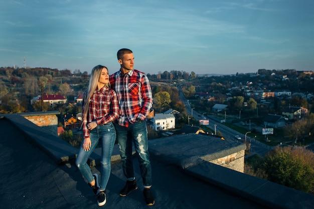La bella coppia innamorata in piedi sul tetto