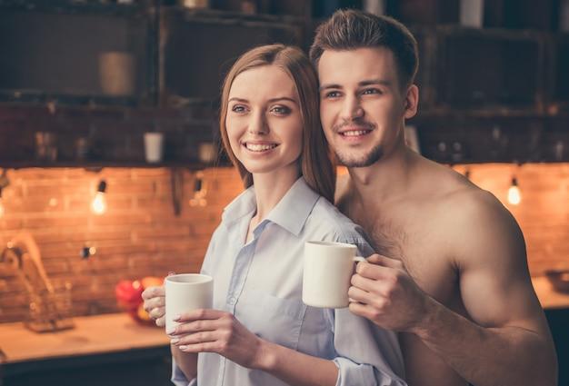 La bella coppia sta tenendo le tazze, abbracciando e sorridendo.