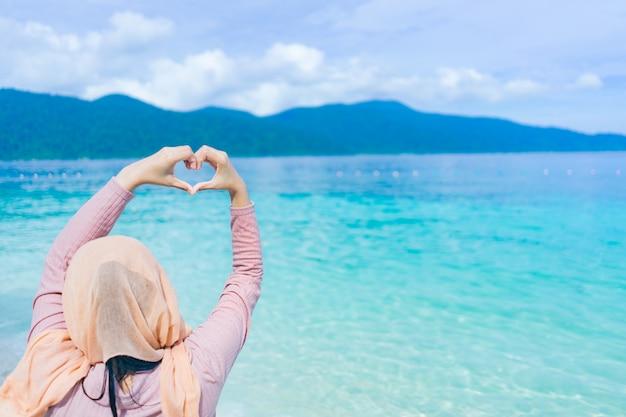 La bella della mano felice dell'ascensore della giovane donna che mostra il cuore modella all'isola della tailandia del lipe con l'acqua dell'oceano del turchese