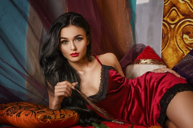 La bella donna alla moda si trova in un veste da camera rosso