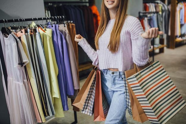 La bella donna alla moda sta camminando nel moderno centro commerciale
