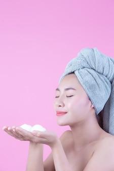 La bella donna asia sta lavando il suo fronte su fondo rosa.