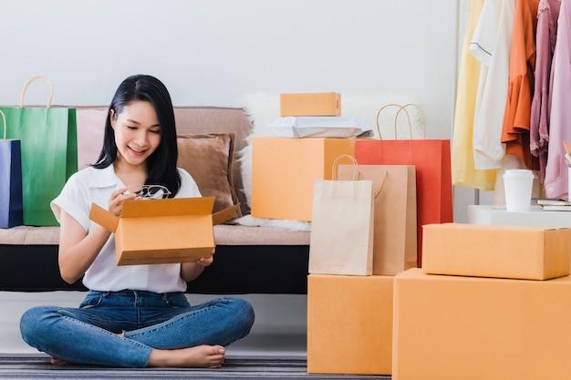 La bella donna asiatica apre la scatola dall'acquisto online a casa con il sacchetto della spesa e la scatola del prodotto.
