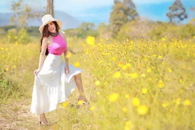 La bella donna asiatica, capelli lunghi in vestito rosa su universo giallo ha archivato nell'inverno con cielo blu e la montagna.