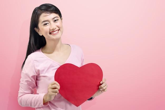 La bella donna asiatica che tiene il cuore rosso modella sulle sue mani