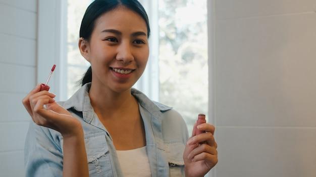 La bella donna asiatica che utilizza il rossetto compone nello specchio anteriore, femmina cinese felice che usando i cosmetici di bellezza per migliorarsi pronta a lavorare nel bagno a casa. le donne dello stile di vita si rilassano a casa