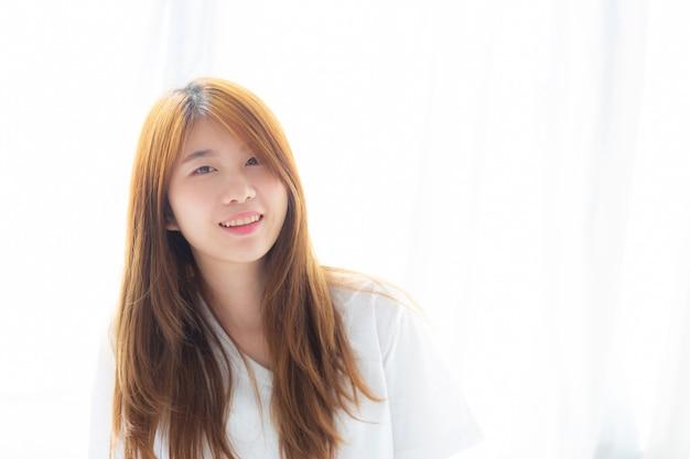 La bella donna asiatica del ritratto che si trova e sorride mentre sveglia