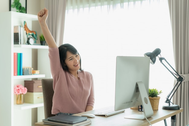 La bella donna asiatica di affari lavora da casa e celebra con il computer, posa felice di successo.