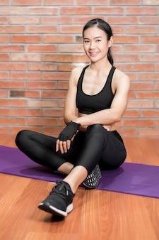 La bella donna asiatica di forma fisica è esercizio a casa
