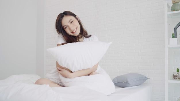 La bella donna asiatica felice sveglia, sorridendo e allungando le sue armi nel suo letto nella camera da letto.