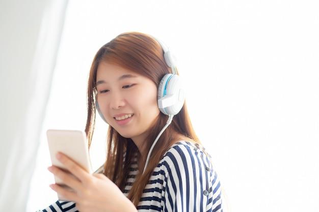 La bella donna asiatica gode di di ascoltare la musica con la cuffia